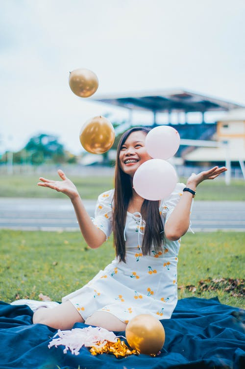 Cheerful Asian woman with balloons on lawn