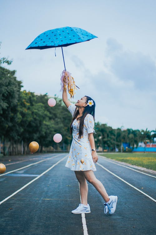 Full body side view of positive ethnic female in dress and sneakers standing on running track with umbrella and pom poms among flying balloons