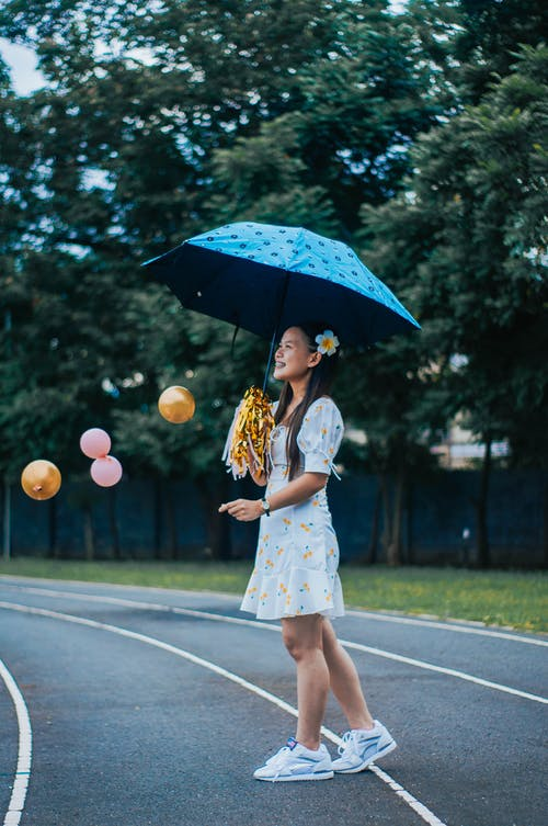 Full body side view of delighted young ethnic female standing with umbrella and pom poms among flying balloons and looking away