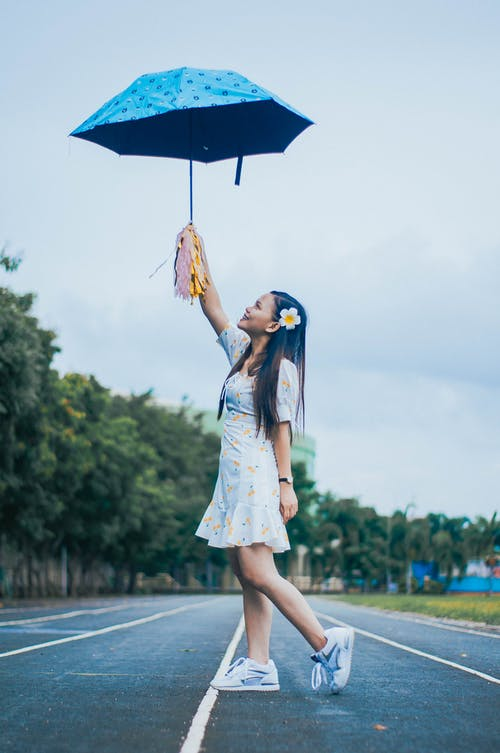 Full body side view of positive ethnic female in dress standing on running track with raised umbrella and pom poms