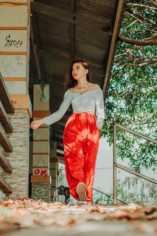 Trendy ethnic teen walking on footpath under house canopy