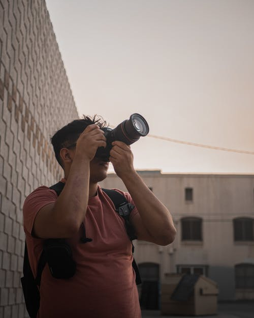 Man taking Photograph with Long Telephoto Lens Camera
