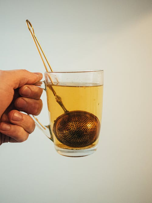 Transparent mug with tea infuser in hand of anonymous person on light background
