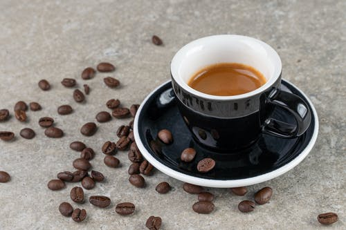 Coffee in Black Ceramic Cup and Saucer with Scattered Beans