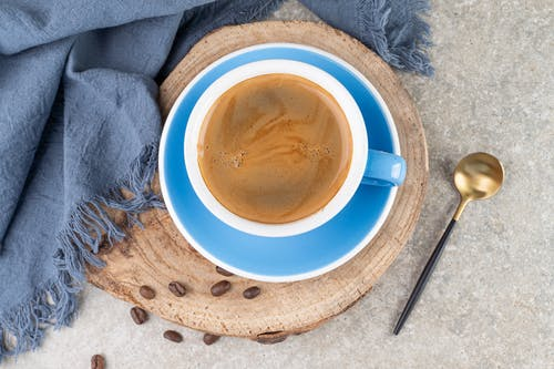 Coffee in Blue Ceramic Cup and Saucer Beside a Spoon