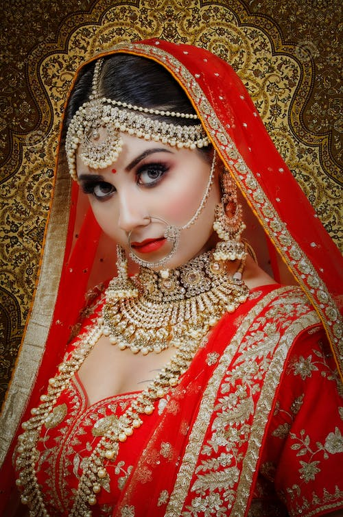 Confident Indian bride in traditional clothes with makeup and accessories