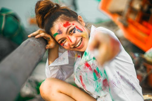 Cheerful young ethnic female in white shirt with bright multi colored flecks of paint pointing finger at camera with bright