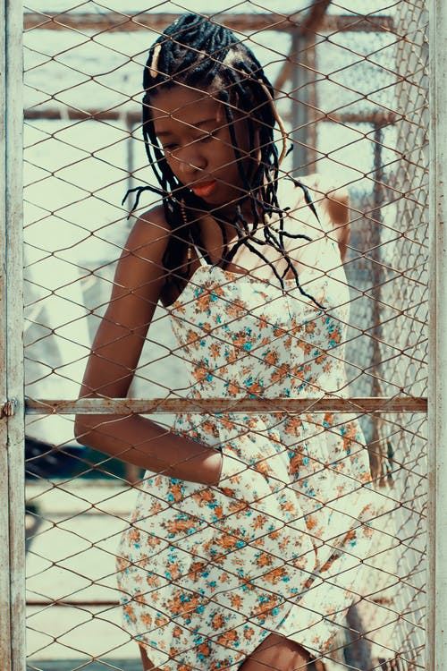 Woman in White and Orange Floral Sleeveless Dress Leaning on White Metal Fence