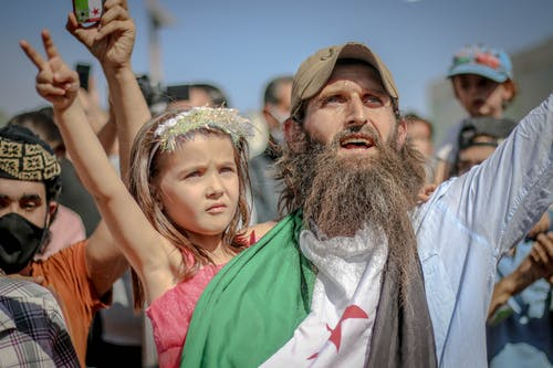 Ethnic bearded man with kid at protest