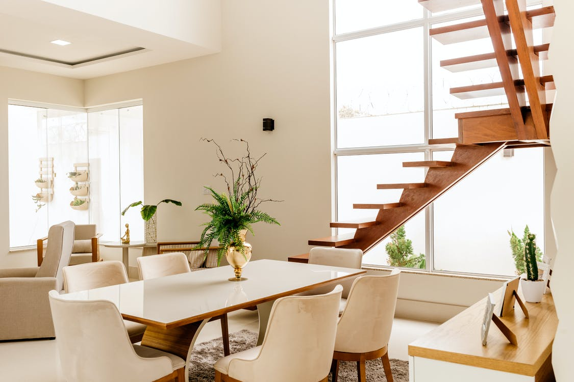 Interior of light living room with wooden stairs and table with comfortable chairs in contemporary house