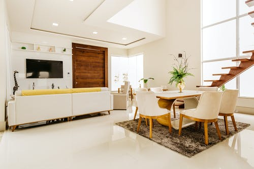 Modern interior of modern living room with second level space in minimalistic design in white color with wooden elements
