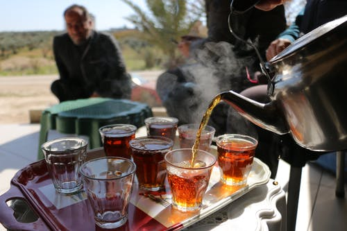 Man pouring tea from kettle into glass cups