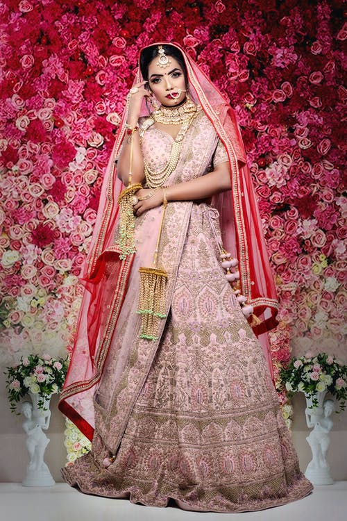 Serious Indian female wearing traditional bridal clothes with accessories