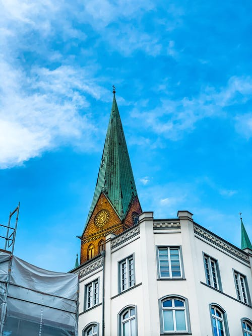 Low Angle View of Church Steeple Under Blue Sky