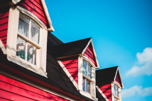 Low angle of similar attic windows of aged residential cottage with red walls under blue cloudy sky