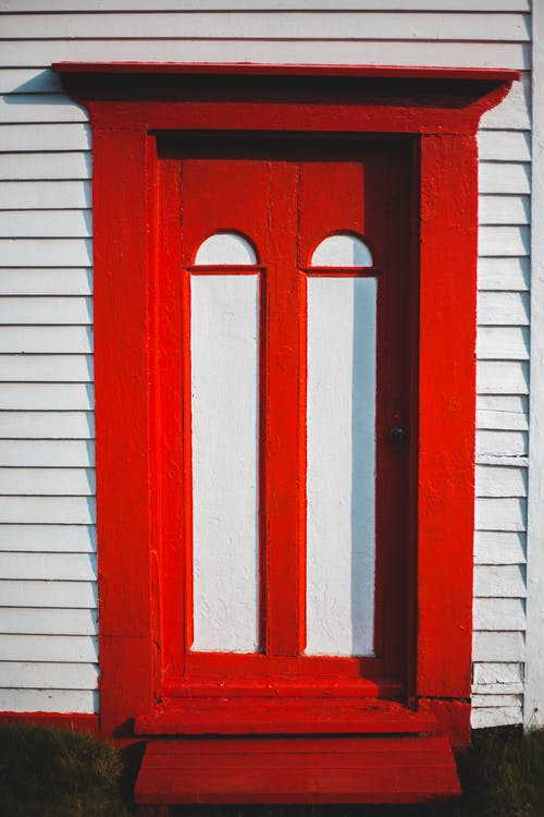 Bright red doorway of residential house with white ribbed walls in suburban area in summer