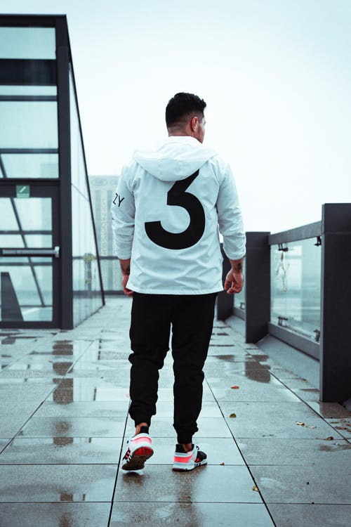 Man in White and Black Nike Hoodie Standing on Gray Concrete Floor