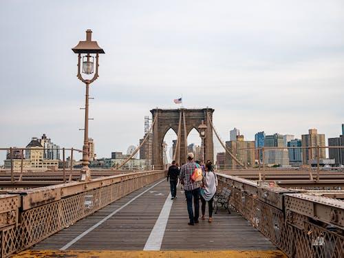 Woman in Black Jacket Walking on Bridge