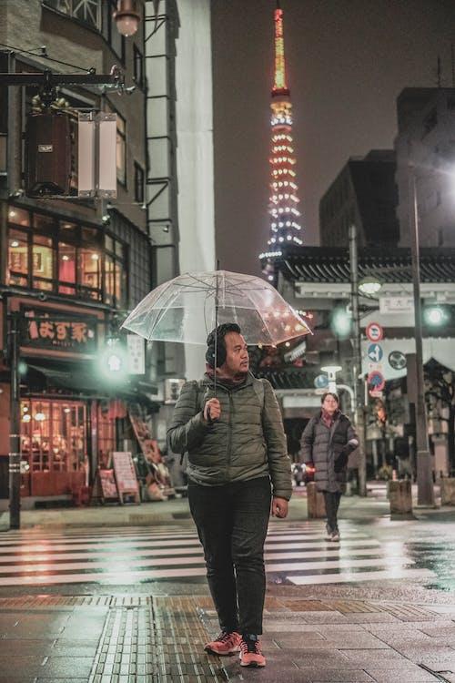 Man Walking on the Sidewalk During Rainy Weather