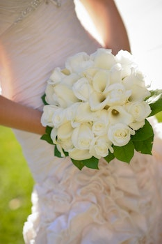 Woman in Wedding Dress Holding White Flower Bouquet
