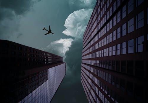 Free stock photo of airplane, cloudy skies, Dark Sky, glass building