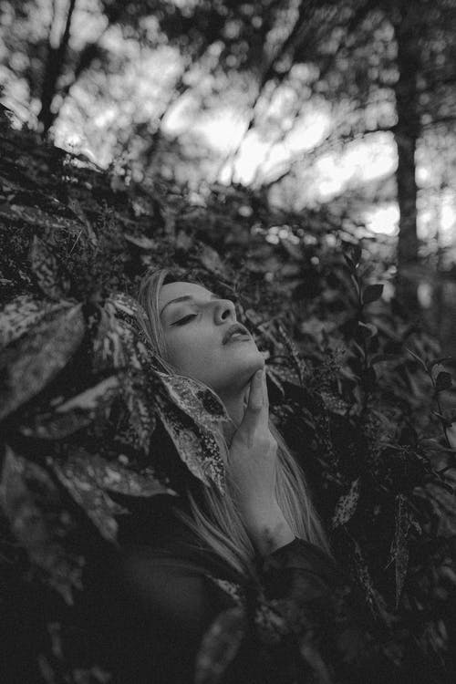 Black and white blond female leaning back while standing in lush foliage of bush in woods