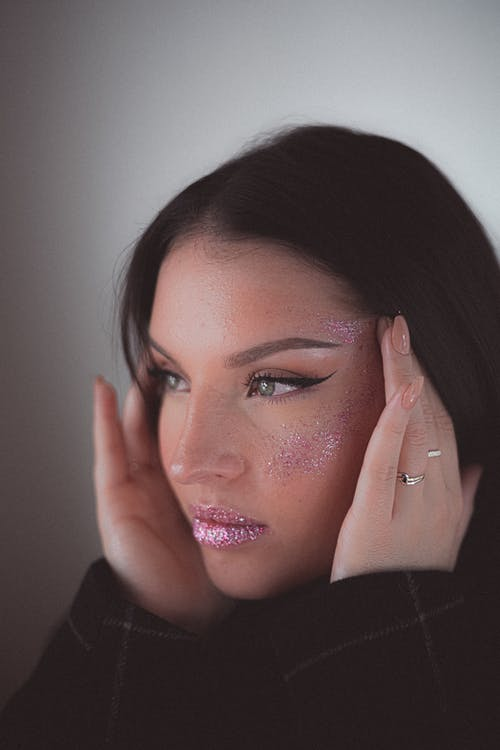 Sensual brunette with makeup and face covered with pink glitters looking away on white background