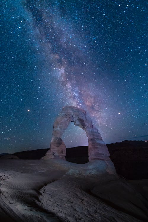 Person Standing on Rock Formation Under Starry Night
