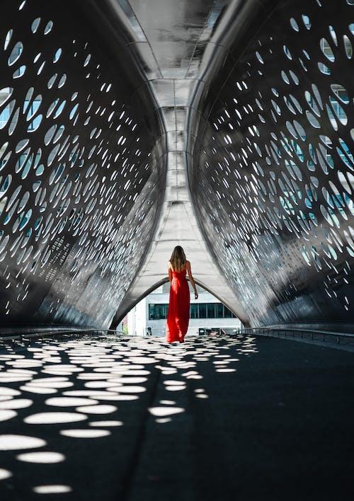 Женщина в красном платье стоит на туннеле