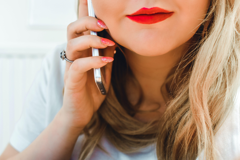 Closeup Photography of Woman Wearing White Shirt Holding Phone