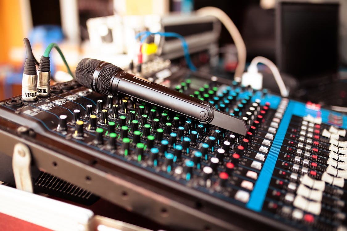 Soft focus of microphone placed on soundboard in sound recording studio at daytime