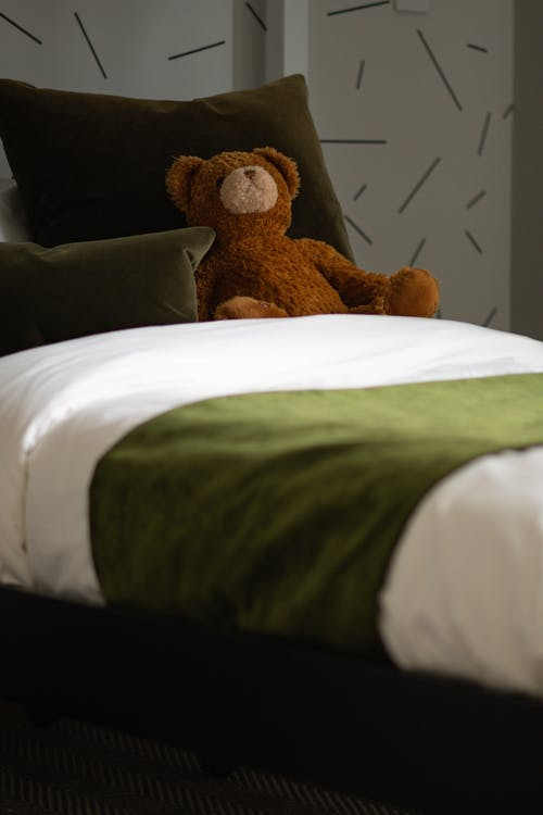 Brown Teddy Bear on White Bed
