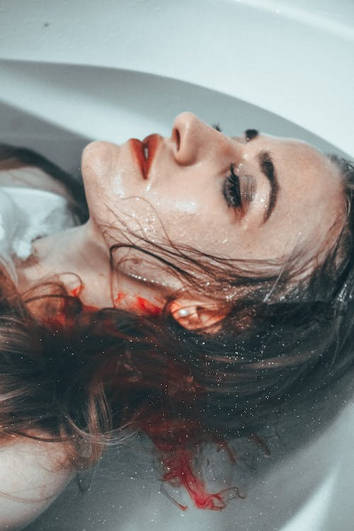 From above of female with wet face and drops of blood lying in water of bathtub
