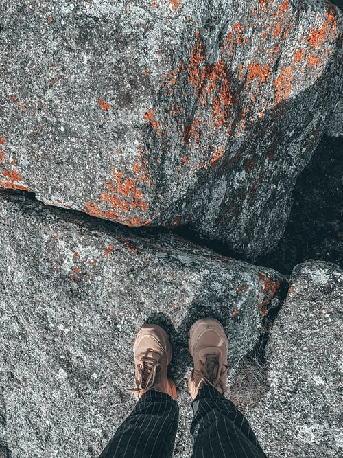 Top view of anonymous crop person in trousers with stripes standing on rocky formation