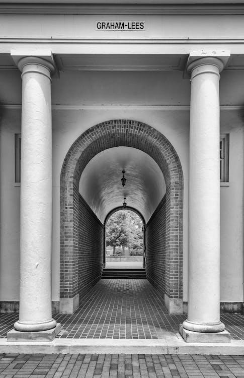 Grayscale Photo of Concrete Hallway