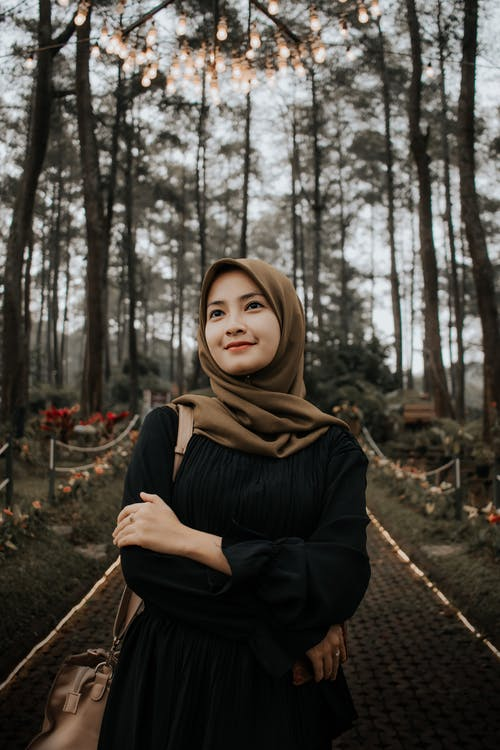 Dreamy young Muslim female in black clothes and headscarf standing with arms crossed on narrow pathway in illuminated park while looking up with smile