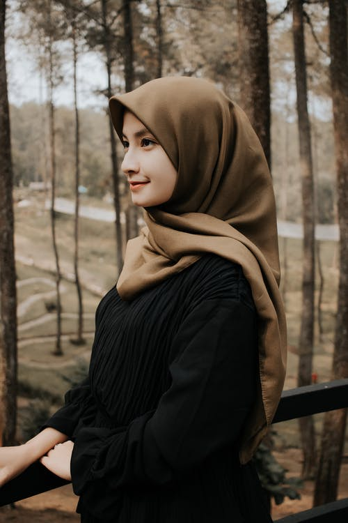 Side view elegant young Muslim female wearing traditional clothes and headdress standing near railing in spacious park while looking away dreamily