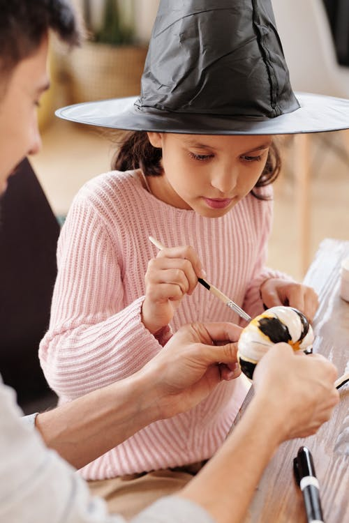 A Girl With A Witch Hat Painting A Pumpkin With Black And White