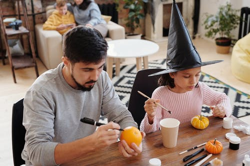 Father And Daughter Decorating Pumpkin And An Orange Fruit