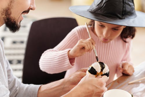 Girl Painting A Pumpkin With Black And White