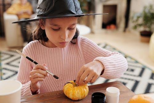 Girl Painting A Small Pumpkin