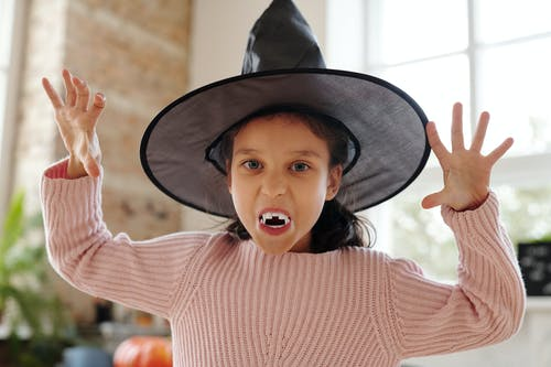 Girl With Vampire Fangs And A Witch Hat Costume