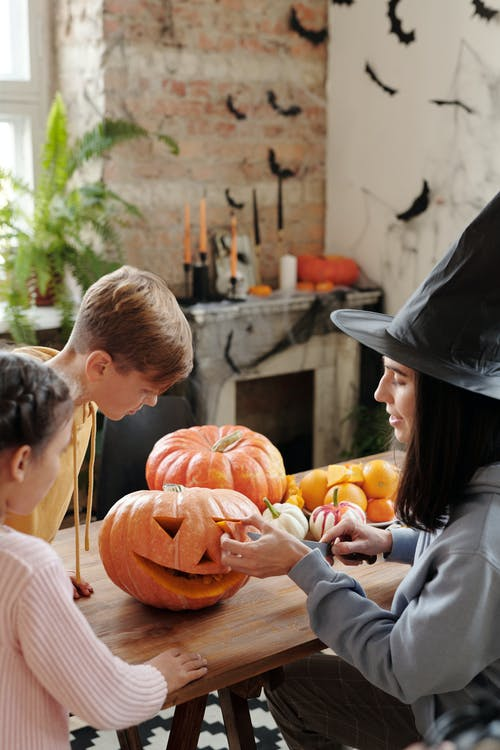 A Mother Carving A Pumpkin While The Children Are Watching