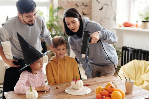 A Family Looking At A Painted Halloween Pumpkin