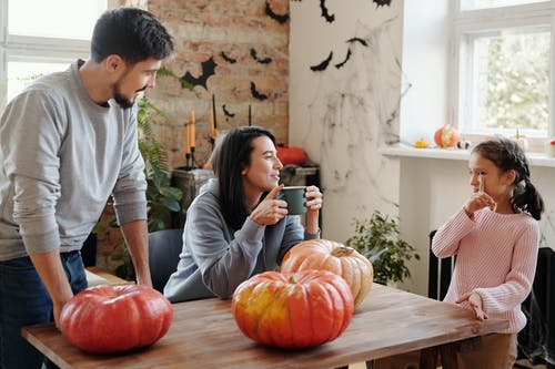 A Happy Family Spending Leisure Time Before Carving Pumpkins