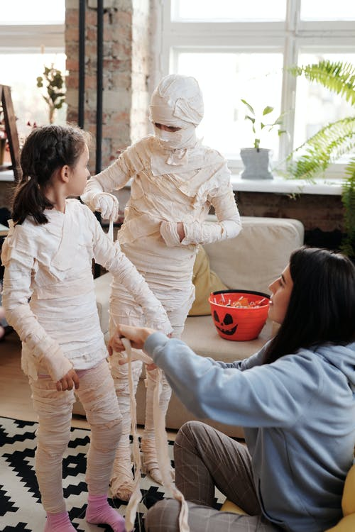 A Mother Helping Her Kids With Their Mummy Halloween Costumes