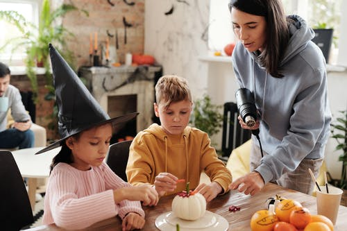 Family Members Decorating A White Pumpkin