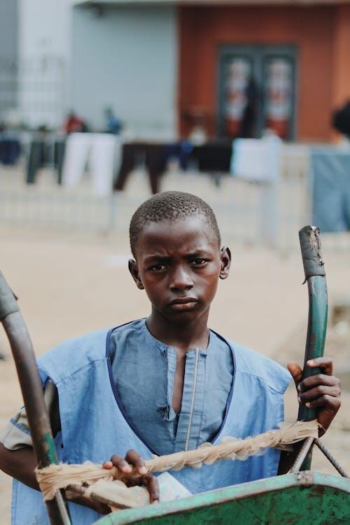 Pensive black boy with weathered wheelbarrow