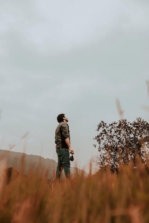 Unrecognizable man standing in grassy field