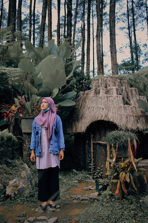 Woman in Blue Robe Standing Near Brown Hut